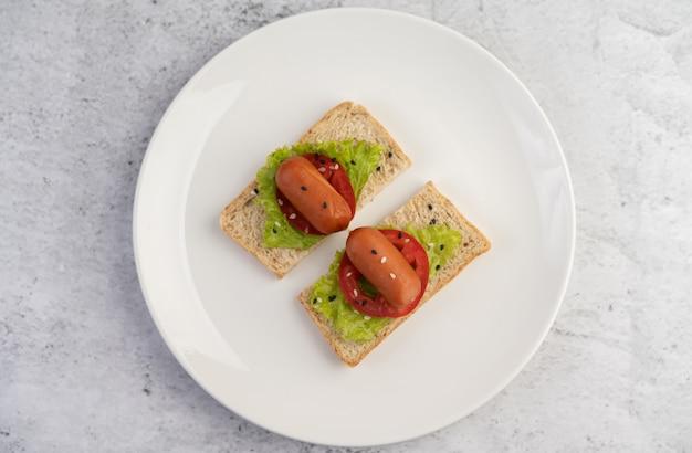 Salsicha com tomate, salada e dois conjuntos de pão em um prato branco.