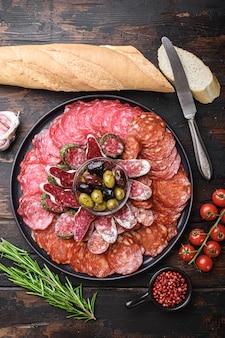 Salsicha curada seca em fatias -chorizo, fuet, salame na mesa de madeira, postura plana.