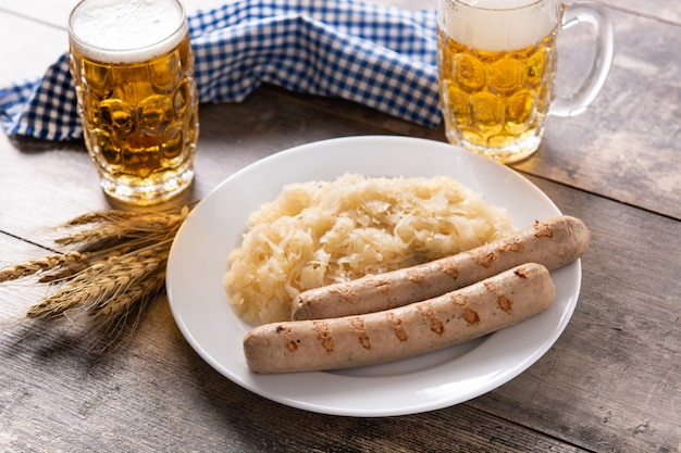 Salsicha de bratwurst, chucrute, pretzels e cerveja na mesa de madeira