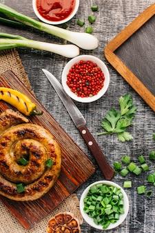 Salsicha de caracol com legumes em fundo cinza