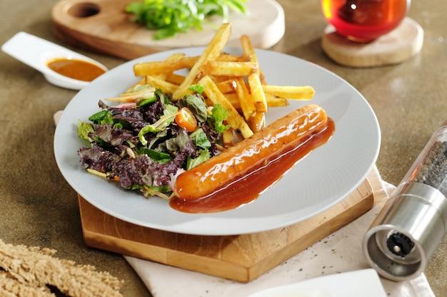 Salsicha de carne grelhada com molho de tomate alemão e batatas fritas