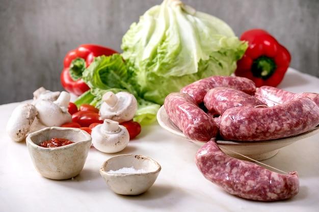 Salsicha de linguiça italiana crua crua no prato na mesa de mármore branco. salada verde, legumes e molho de tomate ao redor.