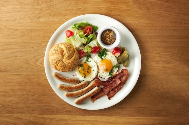 Salsicha de ovo, pão e salada em um grande prato branco sobre uma mesa de madeira café da manhã