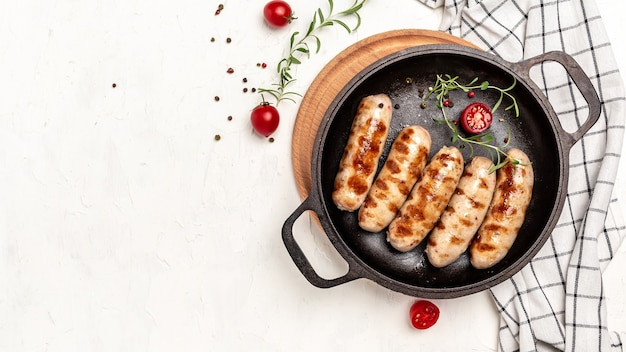 Salsicha de porco frito com ervas em uma panela de ferro fundido. banner, menu, local de receita para texto, vista superior.