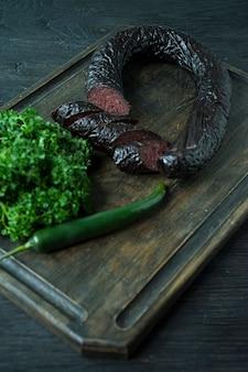Salsicha de sangue em uma placa de estaca escura decorada com salsa encaracolado.