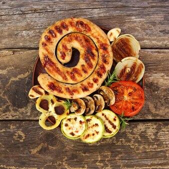 Salsicha e legumes grelhados em fundo de madeira velho. vista do topo. postura plana.