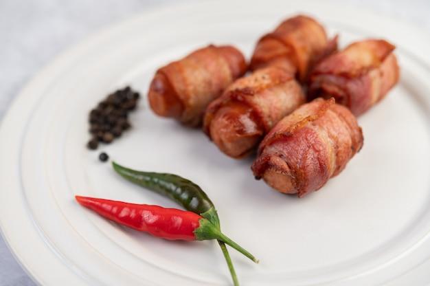 Salsicha envolvida barriga de porco em um prato branco.