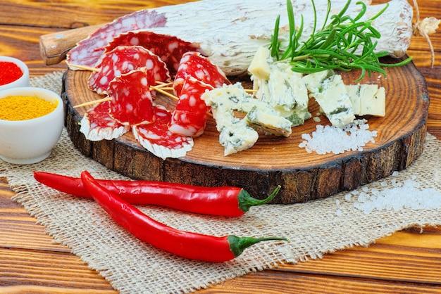 Salsicha fatiada com especiarias e um raminho de alecrim no fundo rústico de madeira escuro.