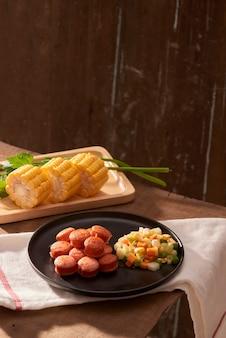 Salsicha fatiada e frita com salada vista de cima de perto