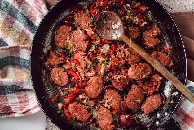 Salsicha fatiada e mistura de legumes frescos fritos na panela rústica com colher no pano de prato.