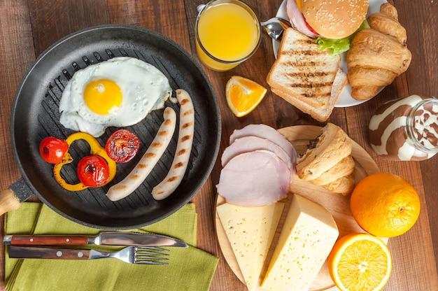 Salsicha frita com ovos e vegetais na frigideira