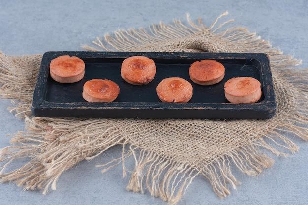 Salsicha frita fatiada na placa de madeira preta.