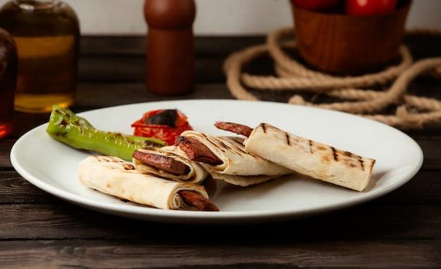 Salsicha frita no pão árabe em uma mesa de madeira