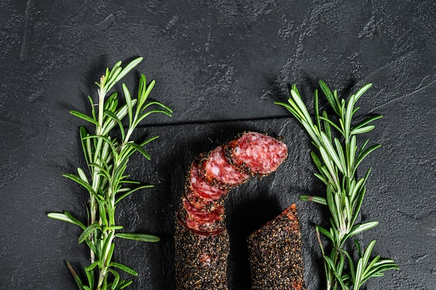 Salsicha fuet cortada em fatias em um prato de ardósia preta com alecrim.