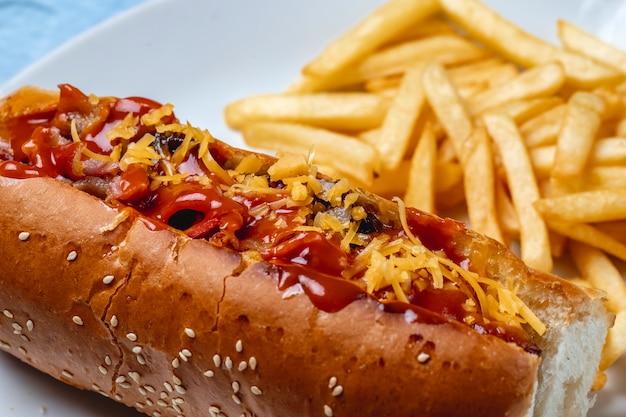 Salsicha grelhada de cachorro-quente de vista lateral com ketchup de queijo de cebola caramelizada e batatas fritas em cima da mesa
