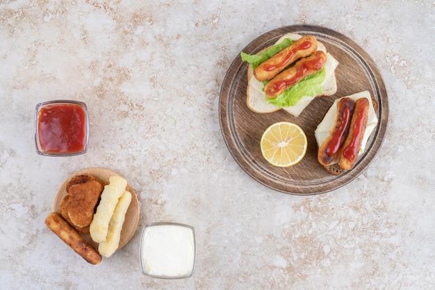 Salsicha grelhada e nuggets de frango em torradas de sanduíche com ervas e especiarias em uma travessa de madeira.