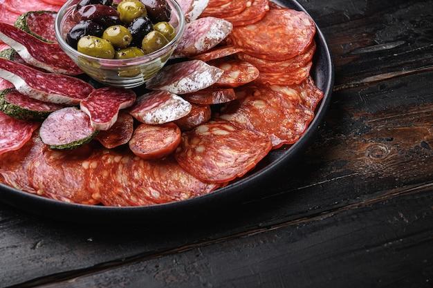 Salsicha seca em fatias de chouriço, fuet, salame na mesa de madeira.