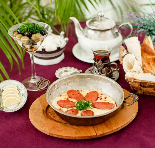 Salsicha turca com ovos em panela de aço, bule de chá, azeitonas e pão