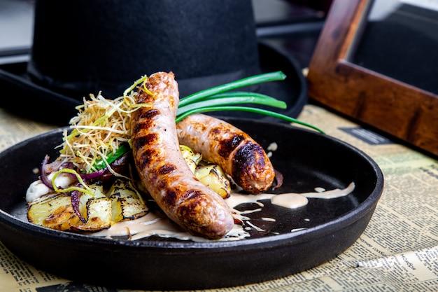 Salsichas alemãs tradicionais com batata servidas na panela. prato de restaurante. vista lateral