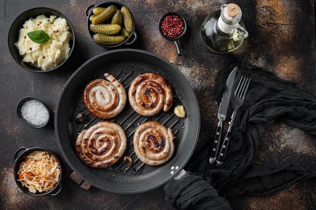 Salsichas alemãs tradicionais com purê de batata e chucrute em frigideira de ferro fundido, em fundo rústico escuro antigo, vista superior plana lay
