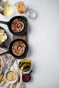 Salsichas alemãs tradicionais com purê de batata e chucrute em frigideira de ferro fundido