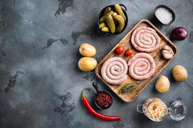 Salsichas alemãs tradicionais com purê de batata e chucrute, em fundo cinza, vista de cima plana, com espaço para texto copyspace
