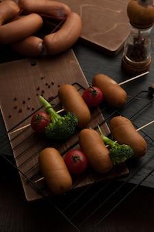 Salsichas assadas com brócolis e tomate