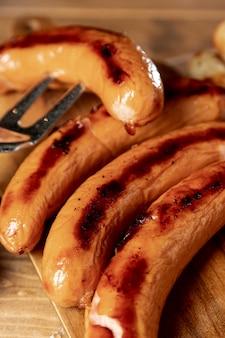 Salsichas assadas com garfo de grelha sobre uma mesa