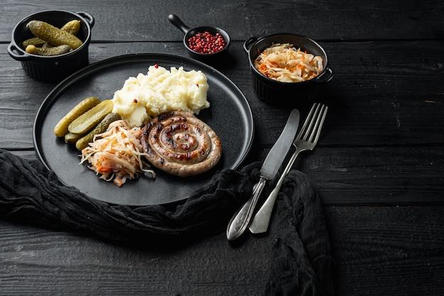 Salsichas assadas com repolho fermentado na mesa de madeira preta