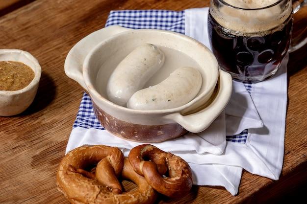 Salsichas brancas tradicionais da baviera de munique em panela de cerâmica servidas com mostarda doce alemã