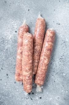 Salsichas bratwurst crus em uma mesa da cozinha. plano de fundo cinza. vista do topo.