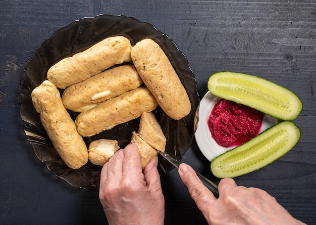 Salsichas caseiras de frango, pepino e molho de raiz de beterraba em uma mesa de madeira