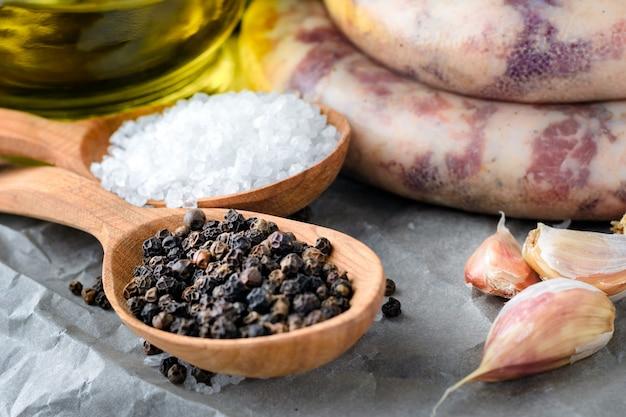 Salsichas caseiras, especiarias, alho e azeite em um fundo cinza. cozinhar em casa