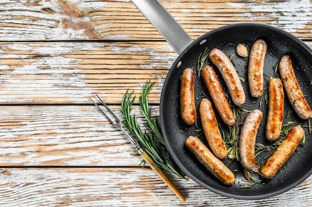 Salsichas caseiras fritas na frigideira, carnes bovina e suína. fundo de madeira. vista do topo. copie o espaço.