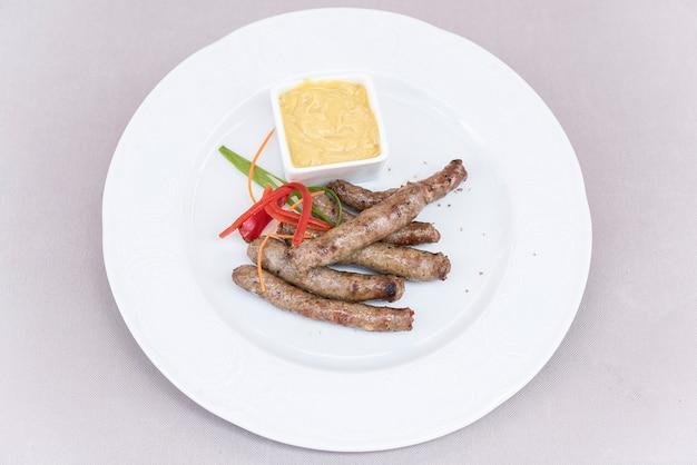 Salsichas caseiras, servido com mostarda e decorado com ervas, isoladas na luz backgro