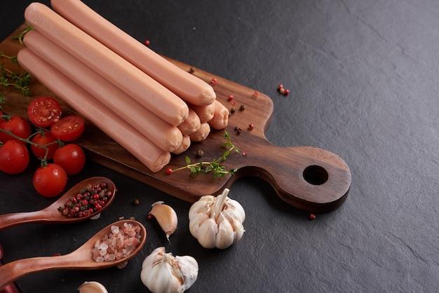 Salsichas clássicas de carne de porco cozida na tábua de cortar com pimenta e manjericão, salsa, tomilho e tomate cereja.