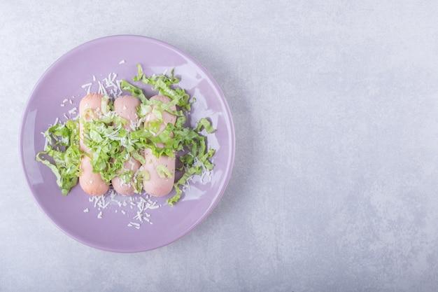 Salsichas cozidas decoradas com alface no prato roxo.