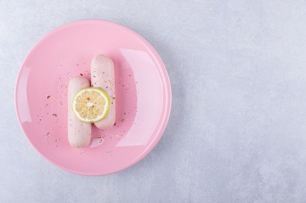 Salsichas cozidas decoradas com limão em uma placa rosa.