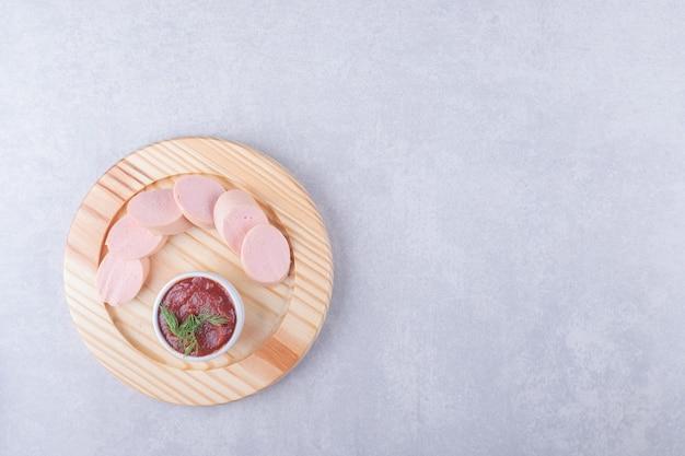 Salsichas cozidas e ketchup na placa de madeira.