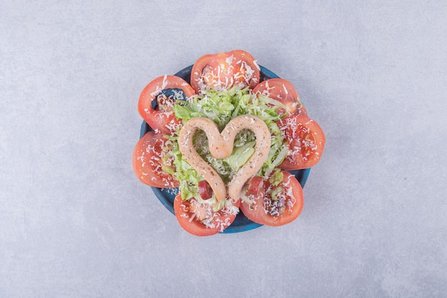 Salsichas cozidas em forma de coração e fatias de tomate.