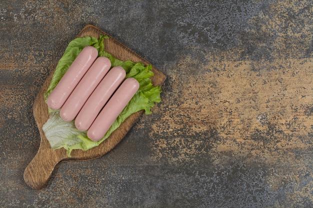 Salsichas cozidas saborosas e alface na placa de madeira.