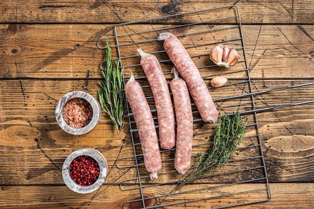 Salsichas cruas - bratwurst com carne de porco em uma grelha. fundo de madeira. vista do topo.