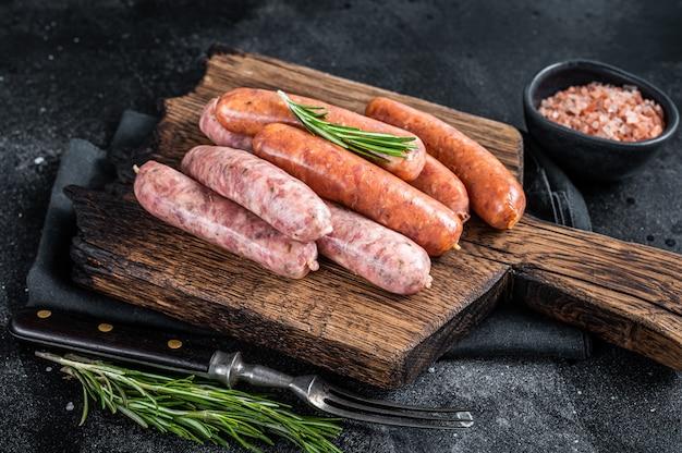 Salsichas cruas cruas chouriço e bratwurst com especiarias na tábua de madeira