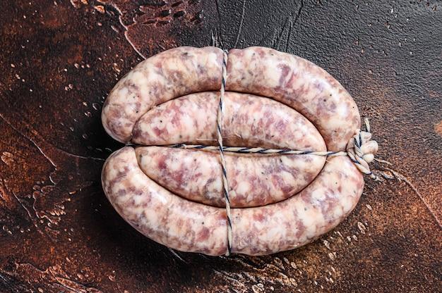 Salsichas cruas de carne de porco e bovina na placa de madeira. vista do topo. fundo escuro.