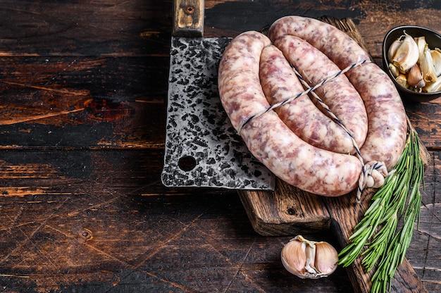 Salsichas cruas de carne de porco e bovina na tábua de madeira