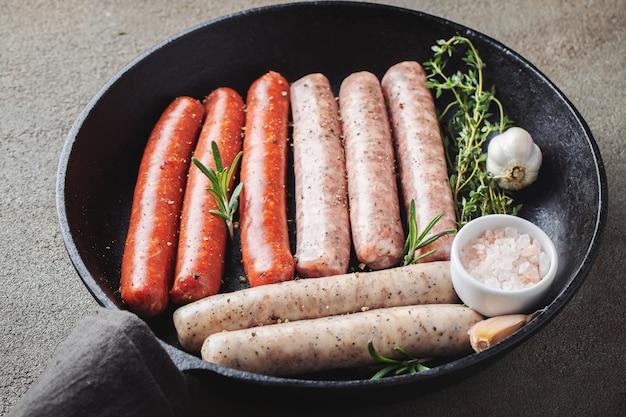 Salsichas cruas frescas sortidos com tomilho, alecrins e alho.