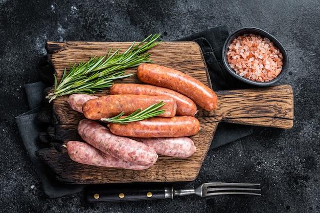 Salsichas crus crus, chouriço e bratwurst com especiarias na placa de madeira. fundo preto. vista do topo.