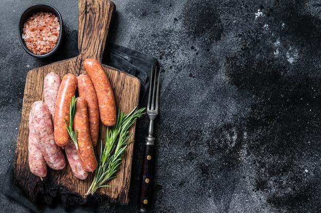 Salsichas crus crus, chouriço e bratwurst com especiarias na placa de madeira. vista do topo.