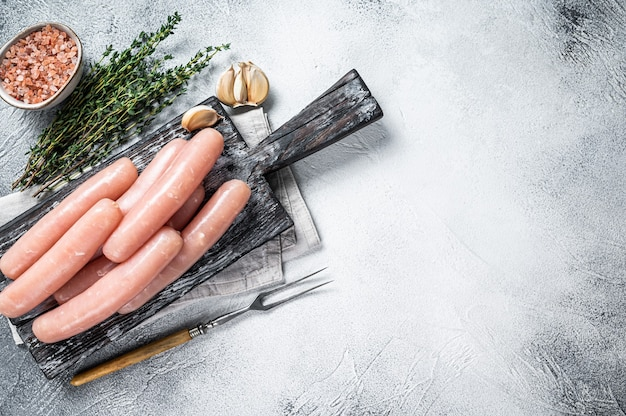 Salsichas crus de carne de frango e peru em uma placa de madeira com tomilho. fundo branco. vista do topo. copie o espaço.