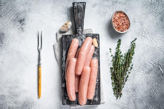 Salsichas crus de frango e peru em uma placa de madeira com tomilho